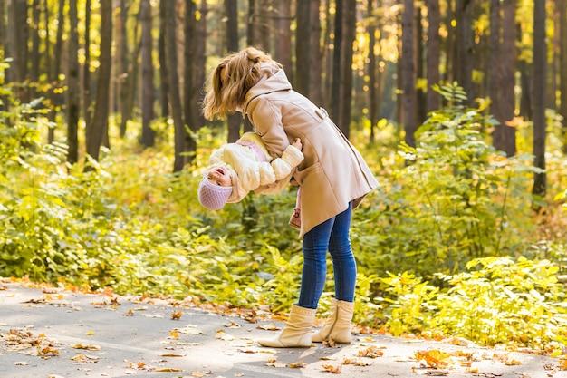 Menina e a mãe brincando no parque outono.