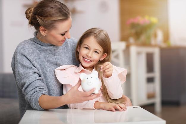 Menina e a mãe dela com o cofrinho sentado à mesa