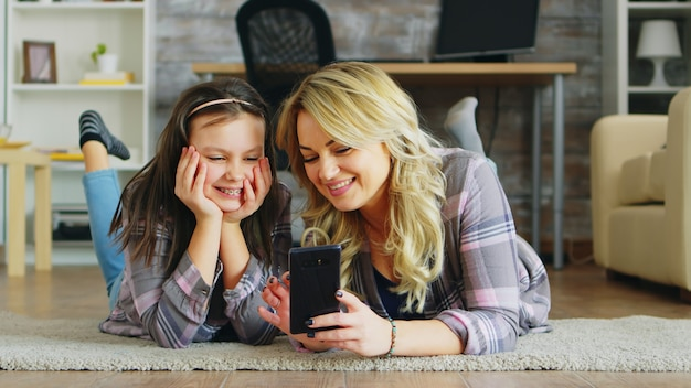 Menina e a mãe dela deitada no chão usando o smartphone para fazer compras.