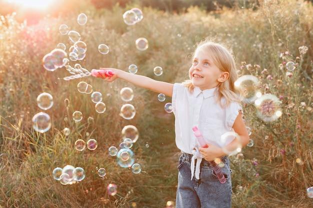 Menina e bolhas de sabão em uma caminhada ao pôr do sol