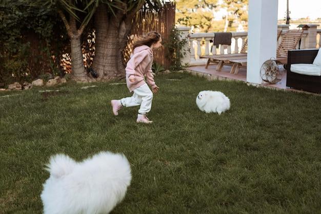 Menina e cachorrinhos brancos fofos brincando ao ar livre