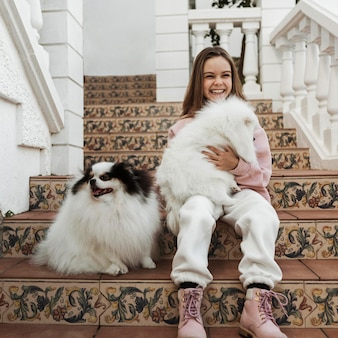 Menina e cachorrinhos brancos fofos sentados na escada