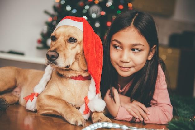 Menina e cachorro deitado junto à árvore de natal
