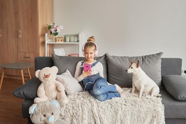Menina e cachorro deitado no sofá em fones de ouvido, ouvindo música com seu smarthphone