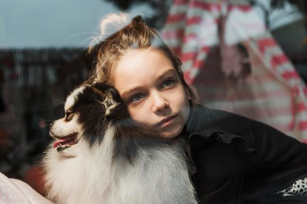 Menina e cachorro dentro de casa