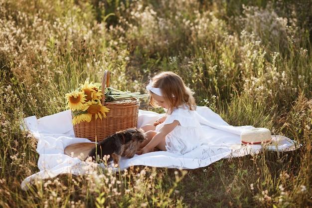 Menina e cachorro em um piquenique no verão