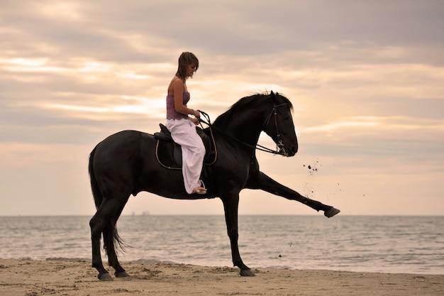 Menina e cavalo na praia
