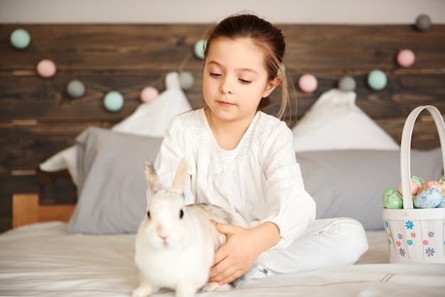 Menina e coelho sentados na cama