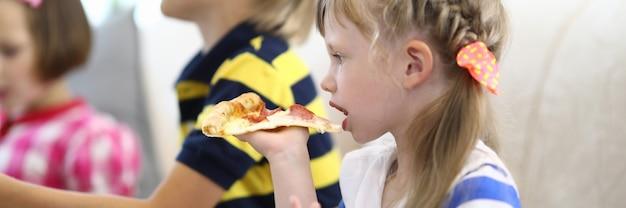 Menina e crianças seguram um pedaço de pizza nas mãos.