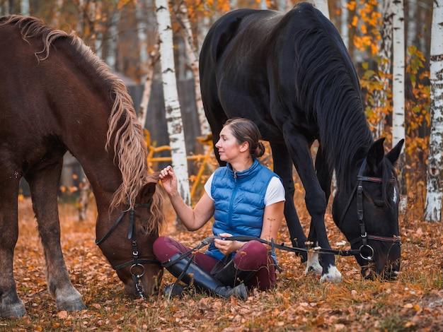 Menina e dois cavalos estão caminhando no parque outono.