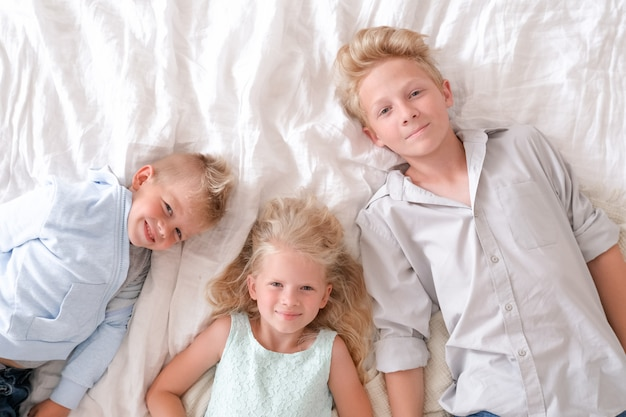 Menina e dois meninos loiros estão juntos na cama, olhando e sorrindo.