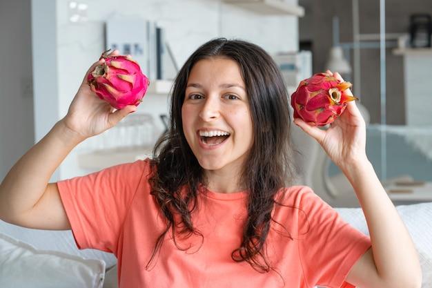 Menina e fruta do dragão. menina alegre, desfrutando de frutas tropicais.