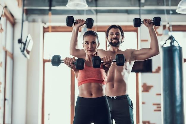 Menina e guy in gym que fazem exercícios dos dumbbells.