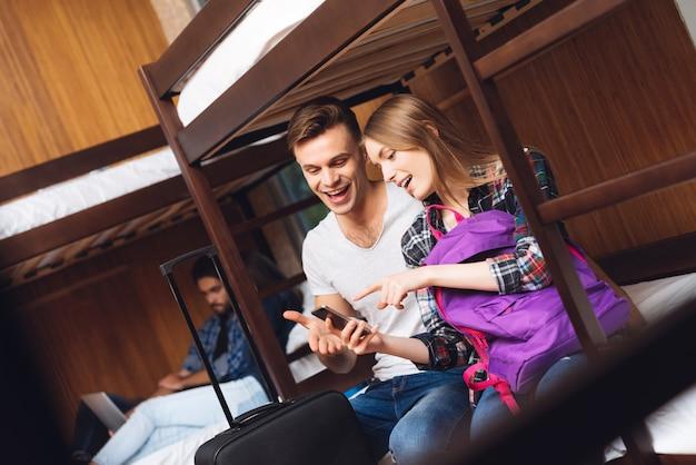 Menina e homem olham para o telefone e riem juntos.