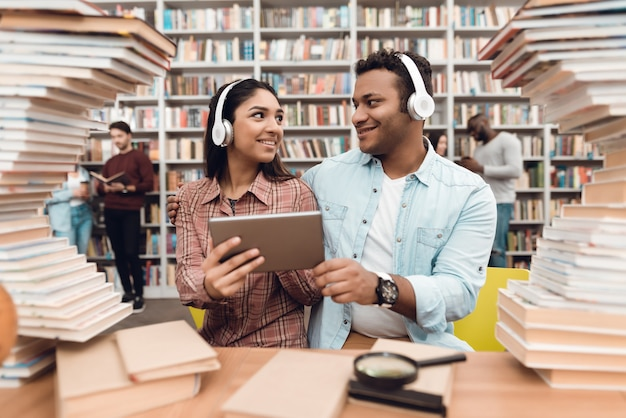 Menina e indivíduo indianos cercados por livros na biblioteca.