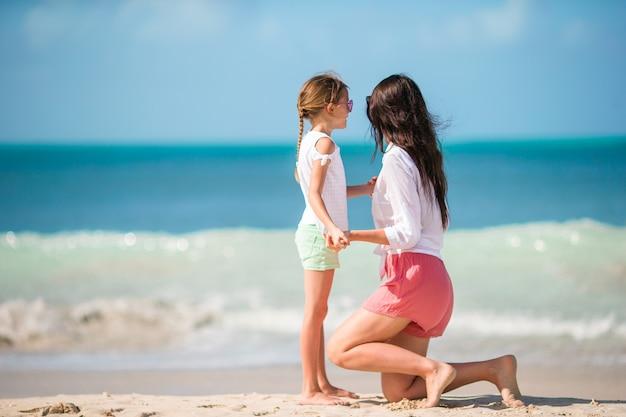 Menina e jovem mãe em férias de praia
