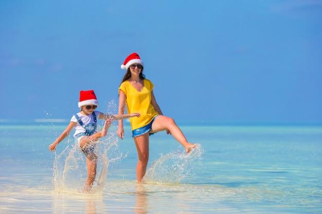 Menina e jovem mãe no chapéu de papai noel durante as férias de praia