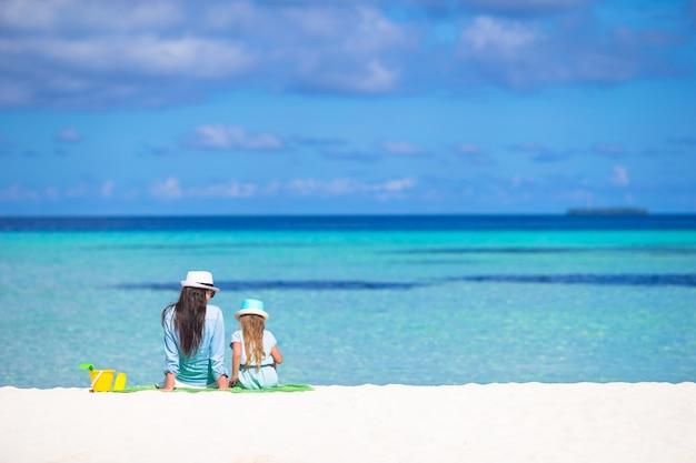 Menina e jovem mãe relaxante na praia durante férias tropicais