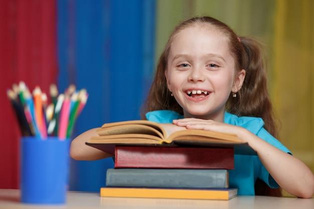 Menina e livro aberto na mesa.