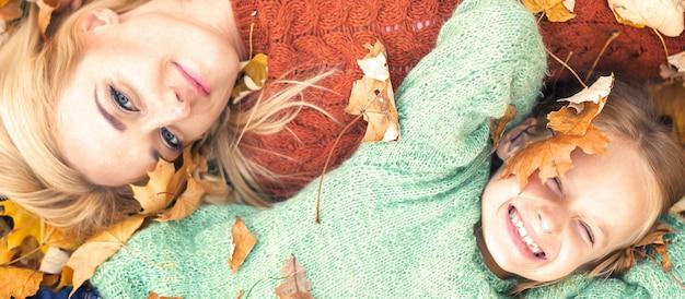 Menina e mãe deitada nas folhas de outono