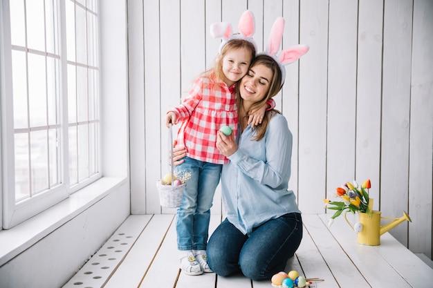 Menina e mãe em pé com cesta de ovos de páscoa