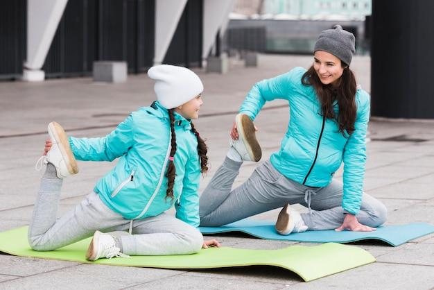 Menina e mãe exercitando na esteira