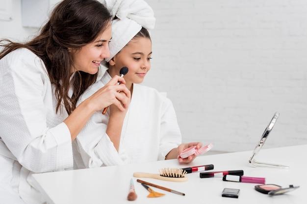 Menina e mãe fazendo sua maquiagem