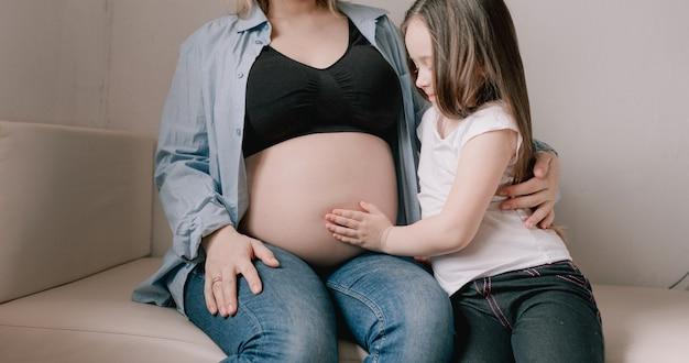 Menina e mãe grávida amando a irmãzinha ao lado da barriga da mãe. família feliz