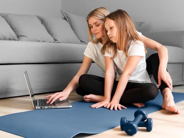 Menina e mãe na esteira assistindo vídeo esporte