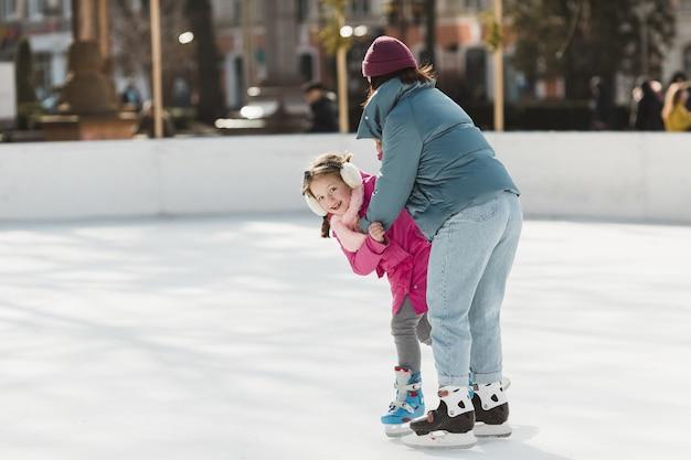 Menina e mãe patinando juntos