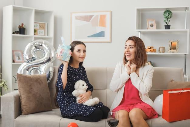 Menina e mãe satisfeitas com um presente e um ursinho de pelúcia com um presente no feliz dia da mulher, sentada no sofá da sala de estar