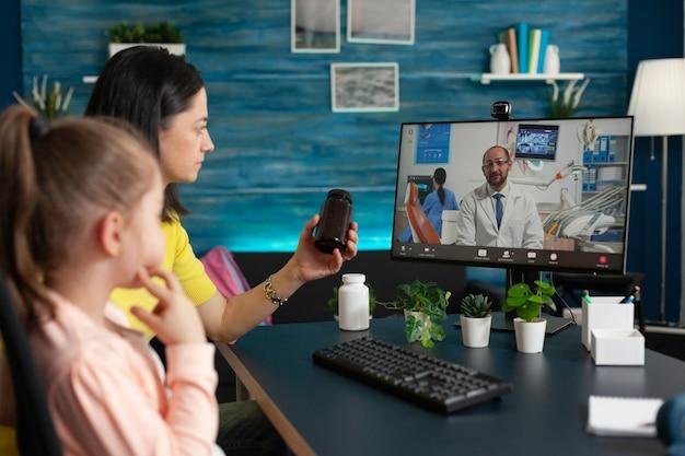 Menina e mãe usando telemedicina para consulta