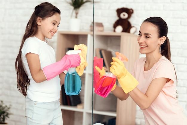 Menina e menina limpar o vidro com detergentes.