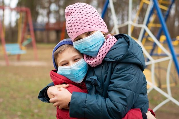 Menina e menino a brincar ao ar livre. crianças com máscaras médicas se divertindo no playground, felizes em brincar ao ar livre após uma longa quarentena