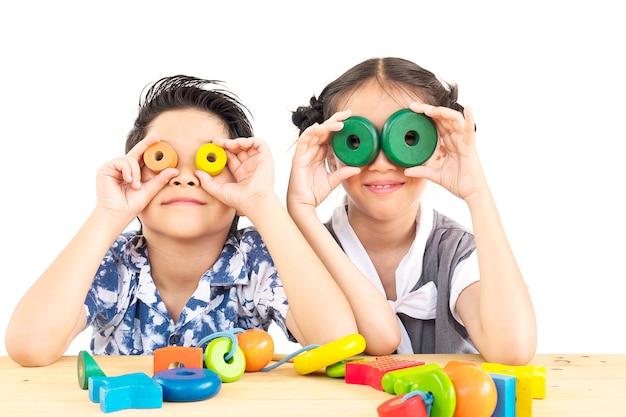 Menina e menino asiático estão alegremente jogando brinquedo colorido bloco de madeira
