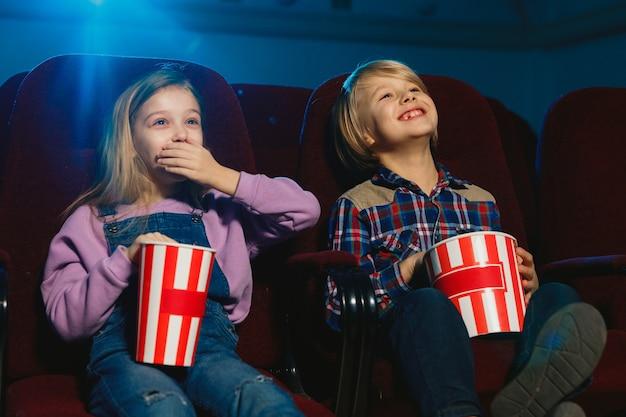 Menina e menino assistindo a um filme no cinema