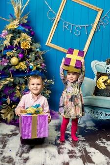 Menina e menino bonitinho estão sorrindo e segurando presentes debaixo da árvore de natal