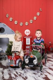 Menina e menino bonito brincam e andam em carros de brinquedo.