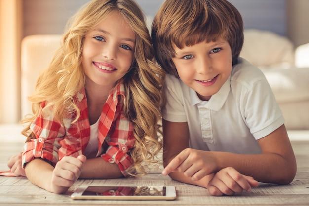 Menina e menino bonitos estão usando um tablet digital