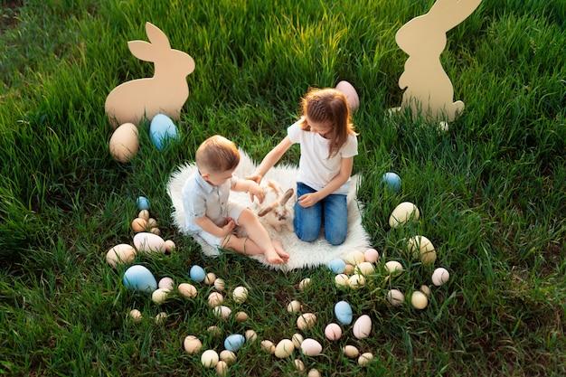 Menina e menino brincam com o coelho rodeado de ovos de páscoa