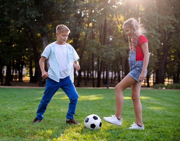 Menina e menino brincando com uma bola na grama