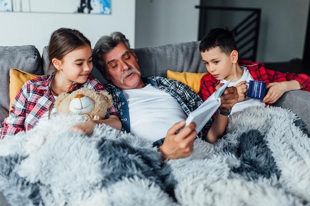 Menina e menino com avô lendo um livro. menina olhando para o livro de conto de fadas.