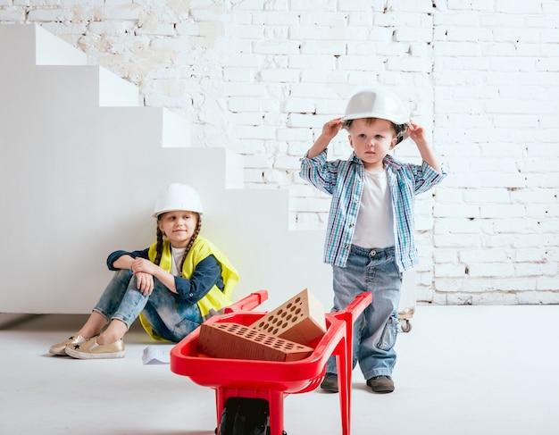 Menina e menino com o carrinho de mão no fundo branco. construção