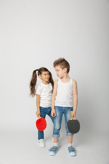 Menina e menino com raquete de pingue-pongue
