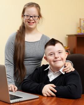 Menina e menino com síndrome de down posam alegremente