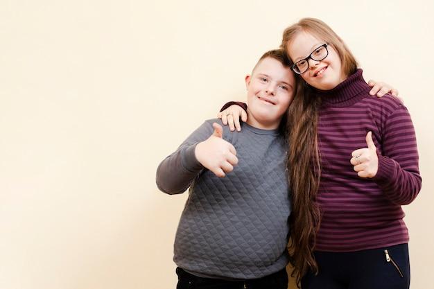 Menina e menino com síndrome de down posando e dando polegares para cima