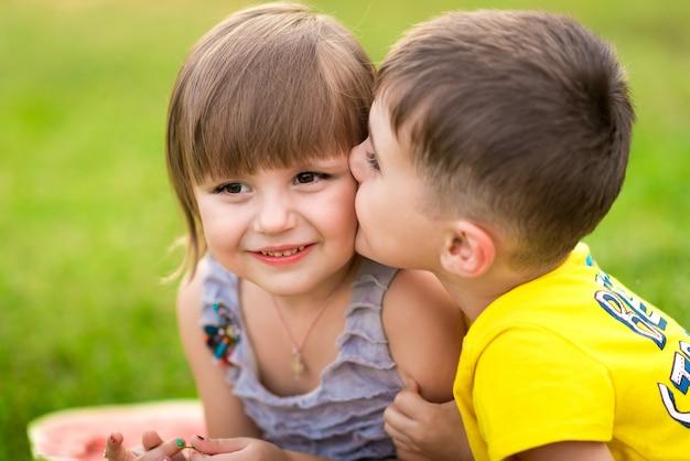 Menina e menino com um pedaço de melancia nas mãos