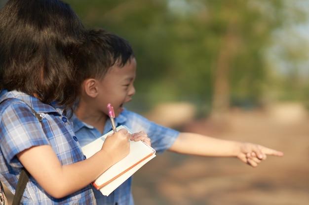 Menina e menino conversam juntos para anotações no livro em uma excursão natural fora da escola