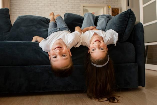 Menina e menino de cabeça baixa no sofá