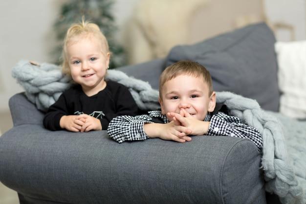 Menina e menino deitado t no sofá coberto com um cobertor de malha cinza e sorrindo